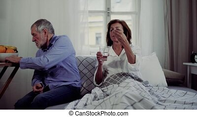A senior couple sitting on bed at home, a man giving...