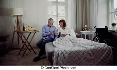 A senior couple sitting on bed at home, a man giving medication to ill wife.