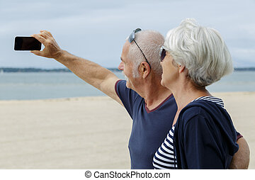 a senior couple taking selfie