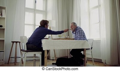A senior couple with a dog sitting at the table at home, having breakfast.
