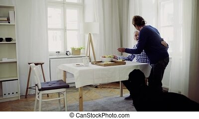 A senior couple with a pet dog having breakfast at the table at home.