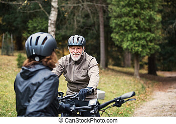 A senior couple with bicycle helmet standing outdoors on a road in park in autumn.