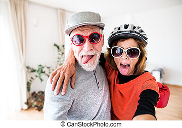 A senior couple with sunglasses having fun at home.