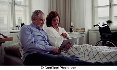 A senior couple with tablet at home, a husband spending time with his ill wife.