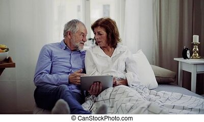 A senior couple with tablet at home, a husband spending time...