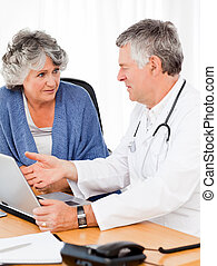 A senior doctor with his patient looking at the laptop