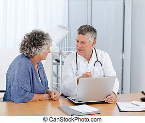 A senior doctor with his patient looking at the laptop in...