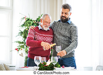 A senior father and adult son pouring wine into a glass at Christmas time.