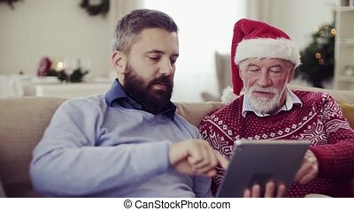 A senior father and adult son with tablet sitting on a sofa at home at Christmas time.
