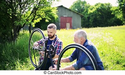 A senior father repairing bicycle with his adult hipster son...