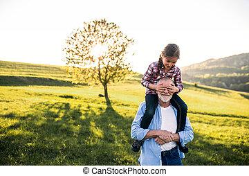 A senior grandfather giving a small granddaughter a...