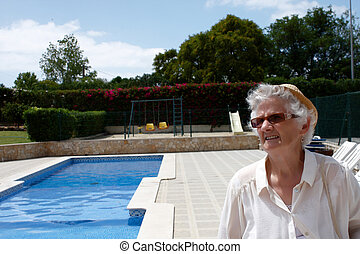 A senior lady standing by the pool
