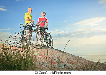 A senior man and a woman bike sunset.