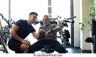A senior man and a young trainer in gym setting smartwatch...