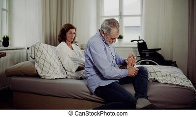 A senior man and his disabled wife sitting on bed, giving a...