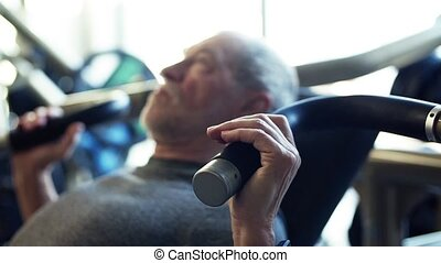 A senior man doing strength workout exercise in gym. Slow motion.