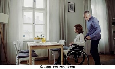 A senior man helping his disabled wife at the table at home....