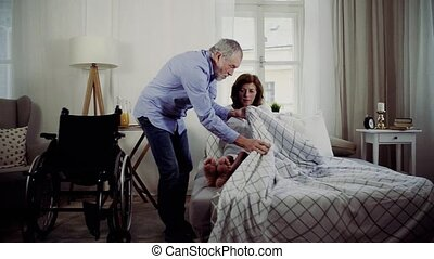 A senior man putting his disabled wife in bed, a husband...