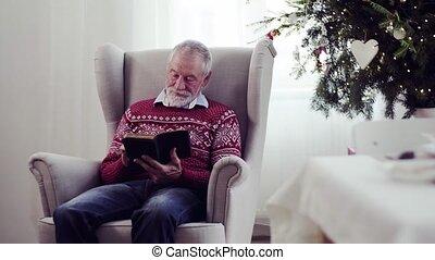 A senior man reading bible at home at Christmas time.