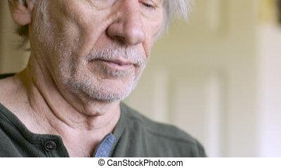 A senior man refills his weekly pill dispenser