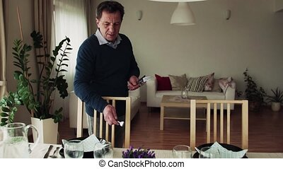 A senior man setting the table for dinner at home. - A...