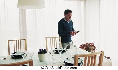 A senior man setting the table for dinner at home.