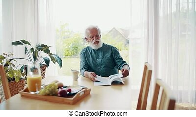 A senior man sitting at the table inside, reading a book.