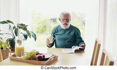 A senior man sitting at the table inside, talking to...