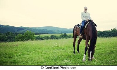A senior man sitting on a horse on a pasture. Slow motion.