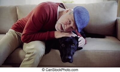 A senior man sitting on a sofa indoors with a pet dog at...