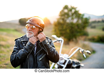 A senior man traveller with motorbike in countryside, putting on helmet.