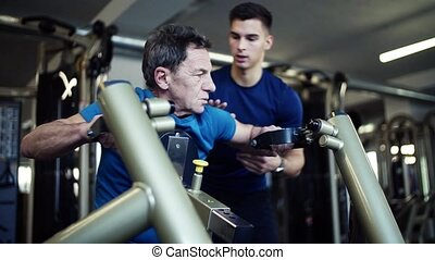 A senior man with a young trainer doing strength workout...