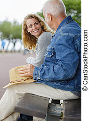 a senior man with adult daughter in the park