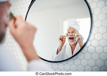 A senior man with cucumber on eyes indoors at home. Copy ...
