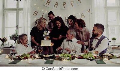 A senior man with multigeneration family celebrating...