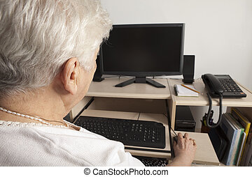 A senior person in front of his computer