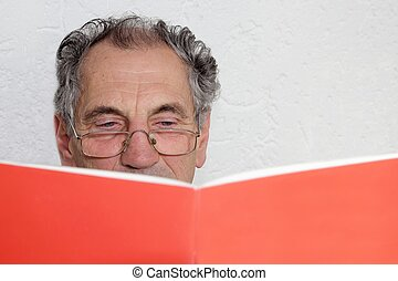 A Senior reading or learning out of a book or magazine -...