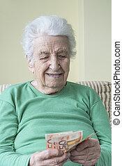 A senior woman counting Euro banknotes