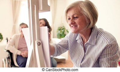 A senior woman drawing at home. - A senior woman with mother...