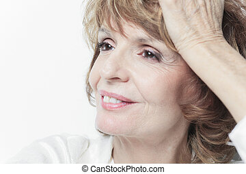 A senior woman in front of white background