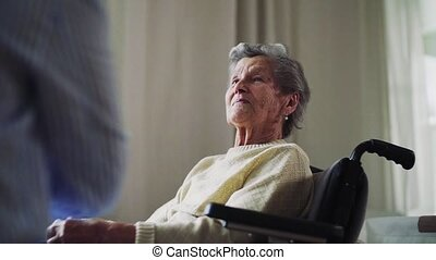 A senior woman in wheelchair talking to a health visitor at home.