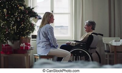 A senior woman in wheelchair with a health visitor at home...