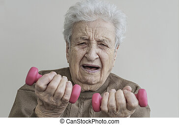 senior woman is difficultly lifting the dumbbells