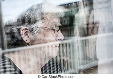 Senior woman looking out through a window like depress