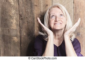 A senior woman pray with a wood background