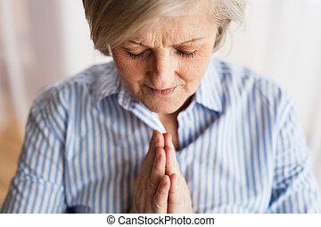 A senior woman praying at home.