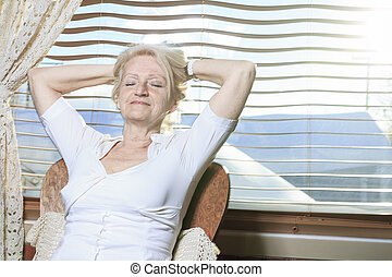 A senior woman relaxing on the kitchen
