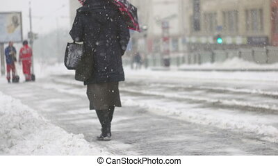 A senior woman walking over pile of snow