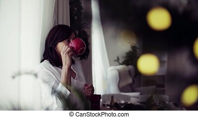 A senior woman with a cup standing by the window at home at Christmas time, drinking.