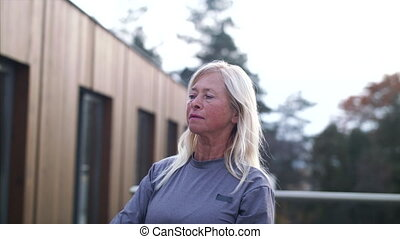 A senior woman with dumbbells outdoors doing exercise.